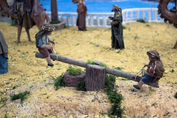 Niños jugando en el balancín del  Belén de la Cofradía del Nazareno de Almuñécar