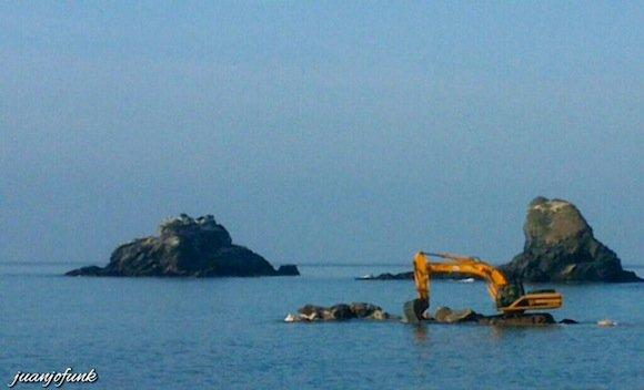 Maquina trabajando en el espigón de Playa Caletilla